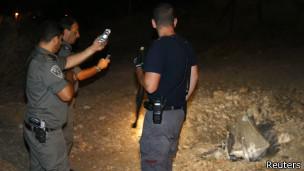 Policías israelíes, cerca de Jerusalén, junto a los restos de un cohete lanzado desde Gaza.