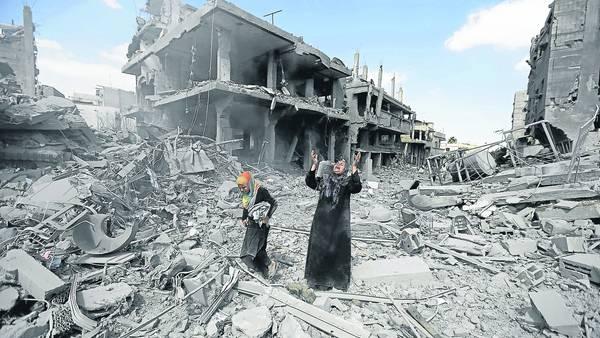 Clamor, incredulidad. La mujer alza los brazos cuando advierte los daños causados por los bombardeos al lugar donde vivía con su familia en Beit Hanun, en el norte de la Franja de Gaza. /AFP