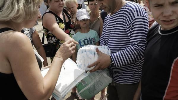 Un hombre distribuye ayuda humanitaria en un campo de refugiados en el este de Ucrania. AFP