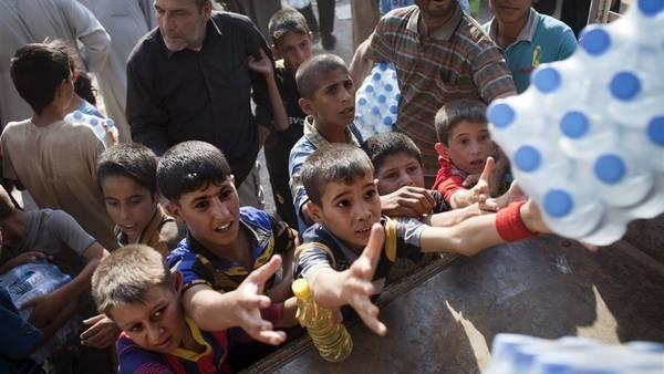 Niños iraquíes reciben ayuda humanitaria en Amerli, luego de que el ejército iraquí logró romper dos meses de bloqueo del Isis.(AFP)