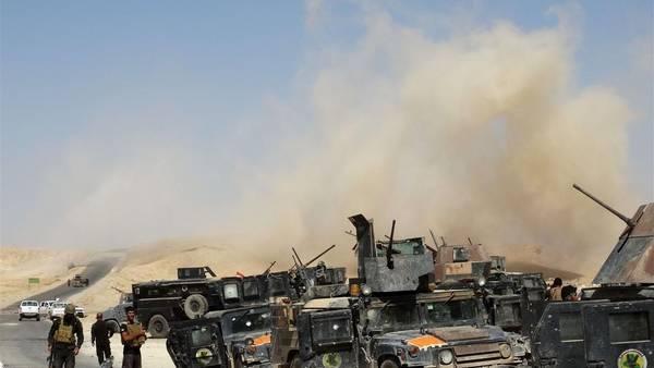 Soldados iraquíes, junto a sus vehículos, ante una cortina de humo tras disparar una ronda de morteros, en la provincia de Anbar. (AFP)