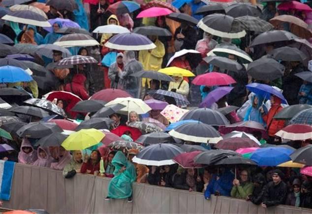 Los fieles esperan bajo la lluvia por la llegada del papa Francico para decir la misa del Domingo de Pascua en la Plaza de San Pedro en el Vaticano, el domingo 5 de abril de 2015.