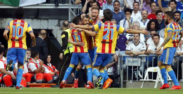 Rodrigo de Pablo, Paco Alcácer y Javi Fuego, de Valiencia, celebran el primer gol del compromiso ante el Real Madrid por la Liga española