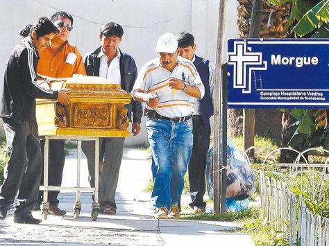 Tristeza. Los familiares de una de las víctimas retiran el cuerpo de la morgue para las posteriores exequias.