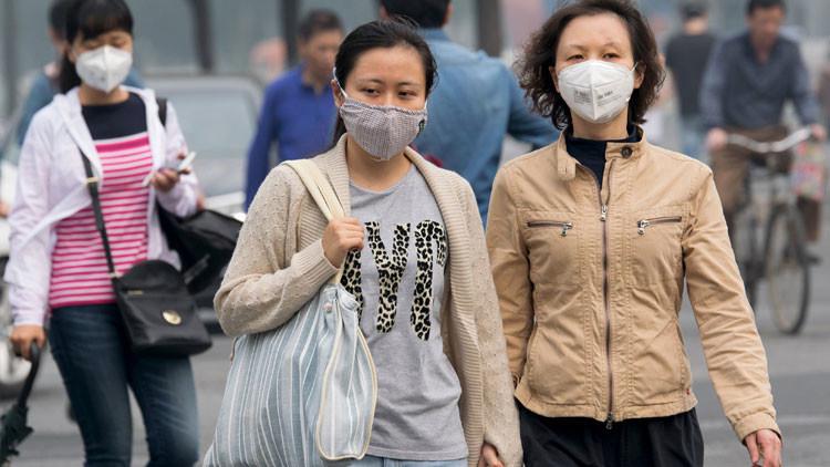 Personas con máscaras protectoras caminan por una calle en Pekín, China