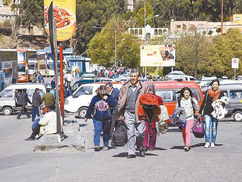Efecto. Una familia camina por el puente de la Autopista. Atrás, el bloqueo con minibuses y carrys.
