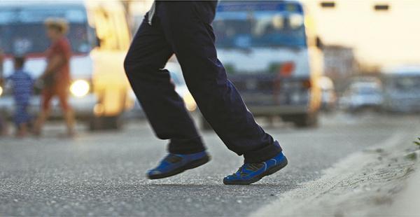 CORRIENDO PARA GANAR A LOS VEHÍCULOS Los pies de este hombre reflejan la carrera para atravesar la vía antes de que los vehículos lleguen hasta donde está el peatón. Los conductores no suelen bajar         la velocidad y confían demasiado en que los peato