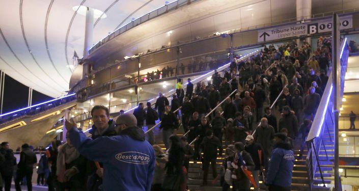 La gente abandonan el Estadio de Francia después de la explosión