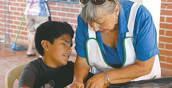 La instructora del taller, Miriam Saavedra, con uno de los niños no videntes que participan del mismo