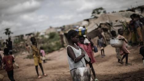 Una joven espera cargar su ración diaria de agua en el campo de desplazados de  Mpoko, en Bangui. / AFP