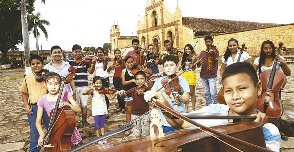 afuera de la parroquia donde tienen   su escuela improvisada con solo dos aulas Niños desde los 4  hasta los 18 años componen   la orquesta de cuerdas de         San José