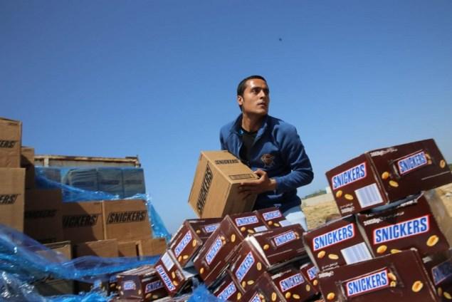 Un trabajador palestino avienta cajas del chocolate Snickers a un hoyo para que sean incendiadas en las afueras de la ciudad de Gaza, el jueves 10 de marzo de 2016. (Foto AP/Adel Hana)