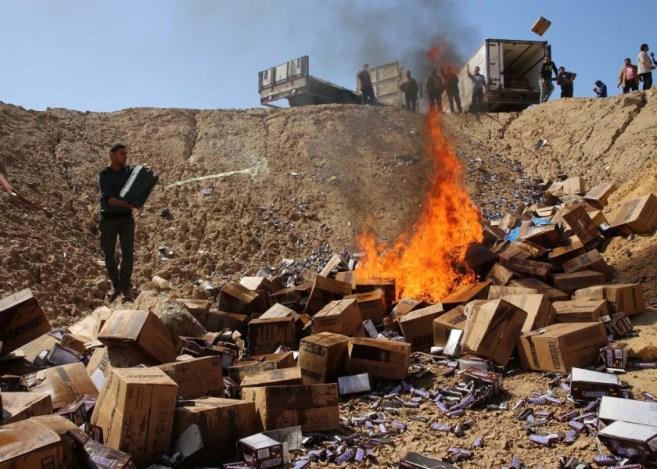 Un trabajador palestino rocía gasolina sobre cajas del chocolate Snickers en las afueras de la ciudad de Gaza, el jueves 10 de marzo de 2016. (Foto AP/Adel Hana)