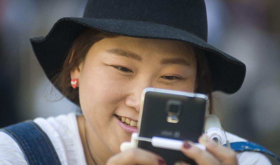Una turista asiática mira su teléfono móvil.