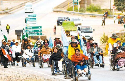 Protesta. La marcha de personas con discapacidad pasa por la población de Parotani, a 50 km de Cochabamba. Foto: Fernando Cartagena
