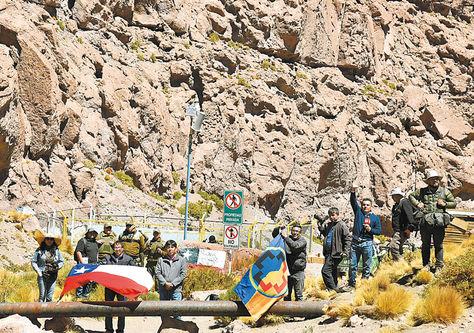 Frontera. El Alcalde de Calama (centro) junto a la bandera de su país, periodistas y carabineros de Chile.