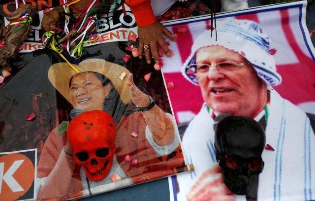 Un chamán con pósters de los candidatos presidenciales en las elecciones peruanas Pedro Pablo Kuczynski y Keiko Fujimori durante una ceremonia adivinatoria en Lima, mayo 30, 2016. Con paso firme, Keiko Fujimori camina al balotaje presidencial del domingo en Perú como la candidata favorita, en un duelo de centroderecha que garantiza el rumbo económico pero podría marcar la vuelta al poder de un apellido que desata tanto amor como odio. REUTERS/Mariana Bazo