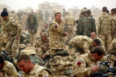 Soldados del 1° Batallón del Regimiento de Paracaidistas Británico se afeitan antes de la primera misión de la mañana, durante la guerra de Irak, en 2003. / AP