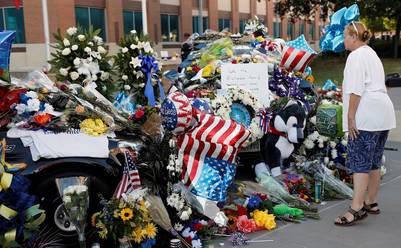 Memorial. Flores y banderas de EE.UU. en un homenaje a los policías asesinados el jueves, frente al Departamento policial en Dallas. /AP