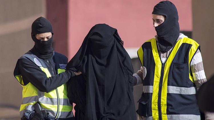 Agentes de policía escoltan a una mujer detenida en Melilla, 16 de Diciembre de 2014