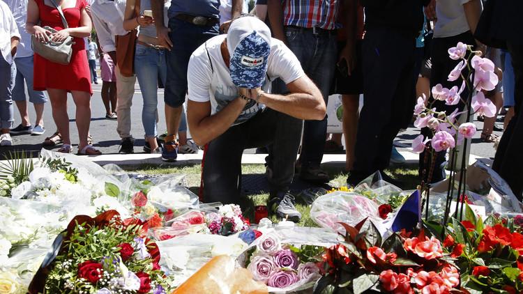 Un hombre ante ramos de flores, mientras la gente se congrega para homenajear a las víctimas del atentado en Niza, 15 de julio de 2016.