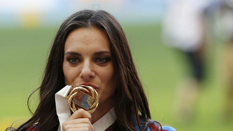 Yelenea Isinbáyeva besa su medalla de oro conseguida en el campeonato mundial de Rusia 2013.