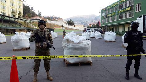 Efectivos policiales antinarcóticos custodian la droga incautada
