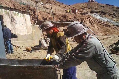 Trabajadores mineros transportan mineral en un campo minero.