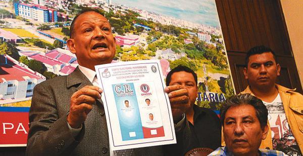 El presidente de la Corte Electoral Permanente, Róger Guzmán, muestra la papeleta de sufragio