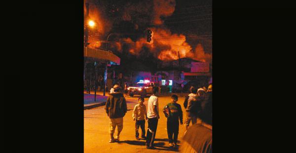 Los pobladores observan de lejos las llamas que salen del mercado