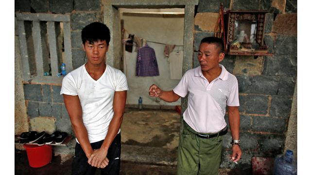 Shi Shenwei (izq), escucha a su tío y capataz Shi Lijia, en una antigua casa de campo que sirve como dormitorio para los trabajadores en una construcción cercana a un templo budista en el pueblo de Huangshan, cerca de Quanzhou, provincia de Fujian, China,