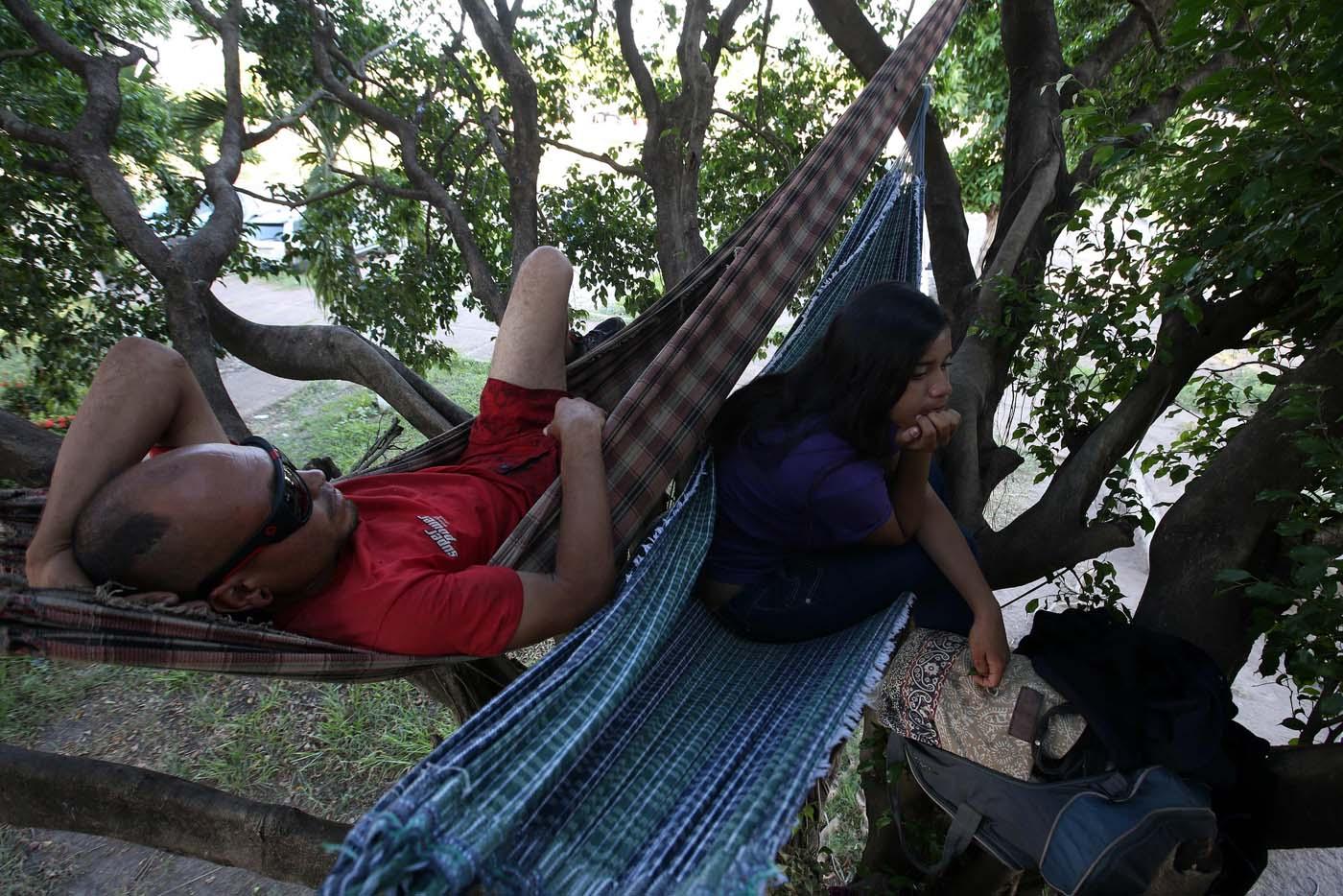 """ACOMPAÑA CRÓNICA: BRASIL VENEZUELA BRA06. BOA VISTA (BRASIL), 22/10/2016.- Los venezolanos José Antonio Garrido (i) y Sairelis Ríos (d) duermen en sus hamacas este jueves, 20 de octubre de 2016, frente a la terminal de autobuses de Boa Vista, estado de Roraima (Brasil). Es venezolana, tiene 20 años, quiere ser traductora y hoy, en una hamaca colgada en un árbol que ha convertido en su casa en la ciudad brasileña de Boa Vista, mece unos sueños que, según aseguró, no serán truncados por """"el fracaso de una revolución"""". """"No estoy aquí por política. Lo que me trajo aquí fue el fracaso de unas políticas"""", dijo a Efe Sairelis Ríos, quien junto a su madre Keila y una decena de venezolanos vive en plena calle, frente a la terminal de autobuses de Boa Vista, una ciudad que en los últimos meses ha recibido unos 2.500 emigrantes de ese país vecino. EFE/Marcelo Sayão"""