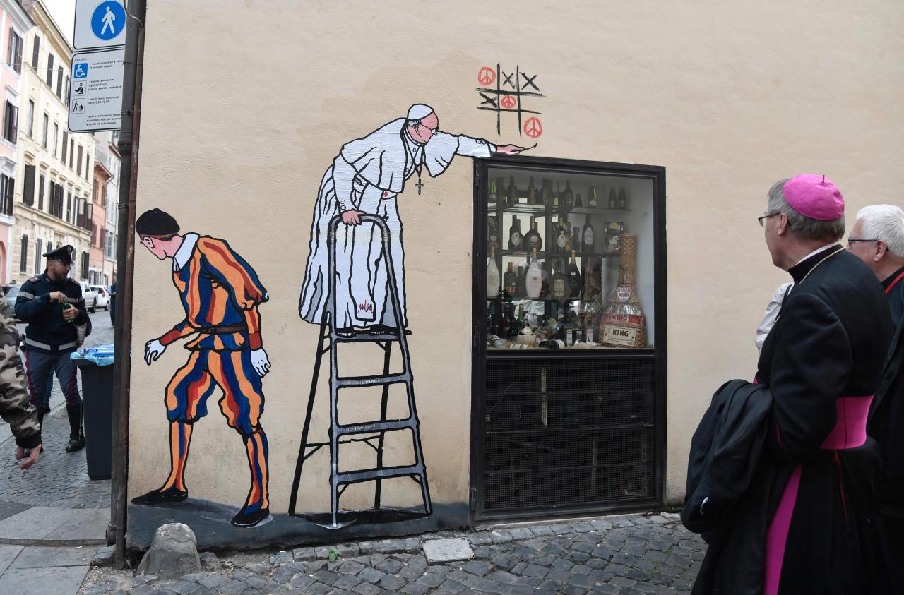 """EL NUEVO GRAFFITI DE FRANCISCO. Maupal, el artista callejero que se hizo famoso cuando realizó el graffiti del """"Superpapa"""", realizó ahora un dibujo de Francisco jugando al Ta-Te-Ti, donde el pontífice gana con el símbolo de la paz. (AFP)"""