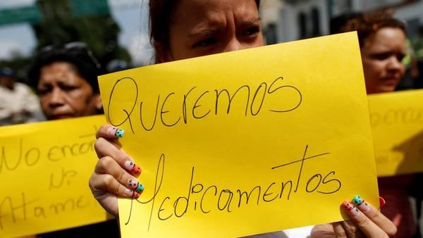 Escasez. Un cartel de simpatizantes opositores pidiendo medicinas durante una protesta contra el gobierno en Caracas (Reuters).