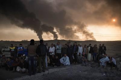 Humo. Habitantes de Qayara, en el sur de Mosul, esperan en un puesto de control de las fuerzas iraquíes. Atrás, el humo de los campos de petróleo incendiados por los yihadistas./ AP