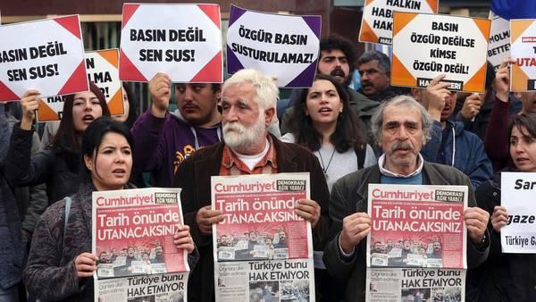 Protesta. Manifestantes muestran ejemplares del diario turco Cumhuriyet, frente a la redacción, en Ankara, en rechazo a los arrestos.  /AFP