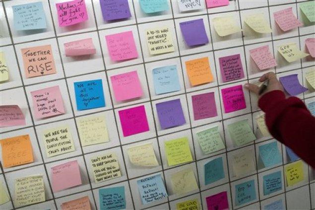 """Un viajero coloca una noa con un mensaje en el muro de la """"Subway Therapy"""", el 11 de noviembre de 2016, en Nueva York. Matthew Chavez, que responde al nombre artístico de Levee, comenzó la instalación en un tunel subterráneo que conecta la línea 1 con la L en la calle 14. En ella anima a los usuarios del servicio a dejar sus sentimientos sobre las elecciones presidenciales escritos en Post-It. (AP Foto/Mary Altaffer)"""