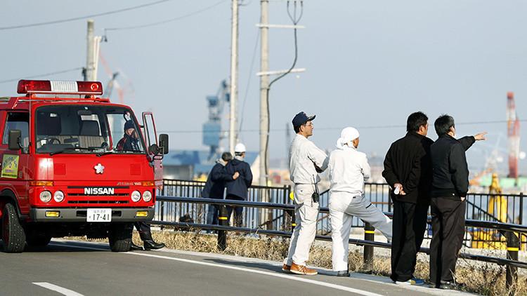 Bomberos y ciudadanos miran hacia el mar después de declararse una alerta de tsunami en la prefectura de Fukushima (Japón).