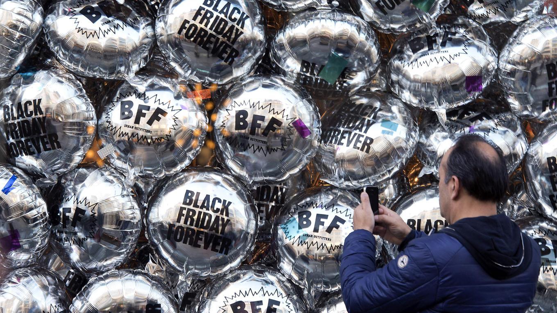 """Un hombre usa un teléfono móvil para fotografiar globos temáticos de """"Black Friday"""" leyendo """"Black Friday Forever"""" y """"BFF"""" formando una vitrina de una tienda minorista en Oxford Street, Londres. Foto: AFP / Justin Tallis"""