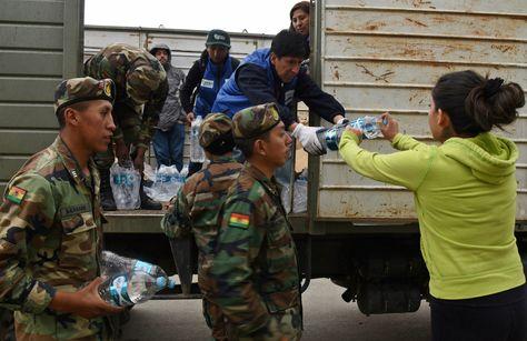 Una vecina afectada por la crisis en La Paz recibe agua embotellada que comenzó a distribuir el Gobierno.
