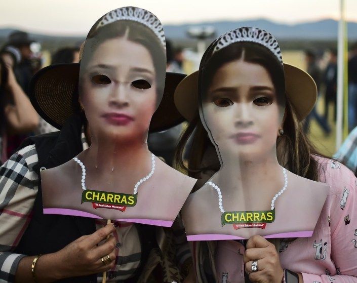 Dos mujeres usando máscaras con el rostro de la cumpleañera (AFP)