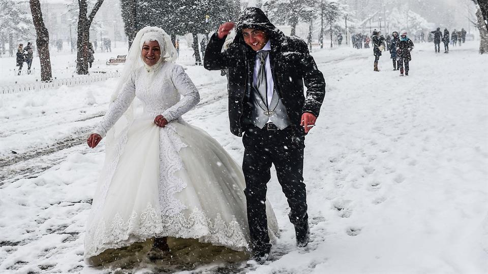 Ni la nieve, ni las extremas bajas temperaturas lograron que ésta pareja de recién casados caminara por la plaza de Sultanahmet, en Estambul. Foto: AFP / Yasin Akgul