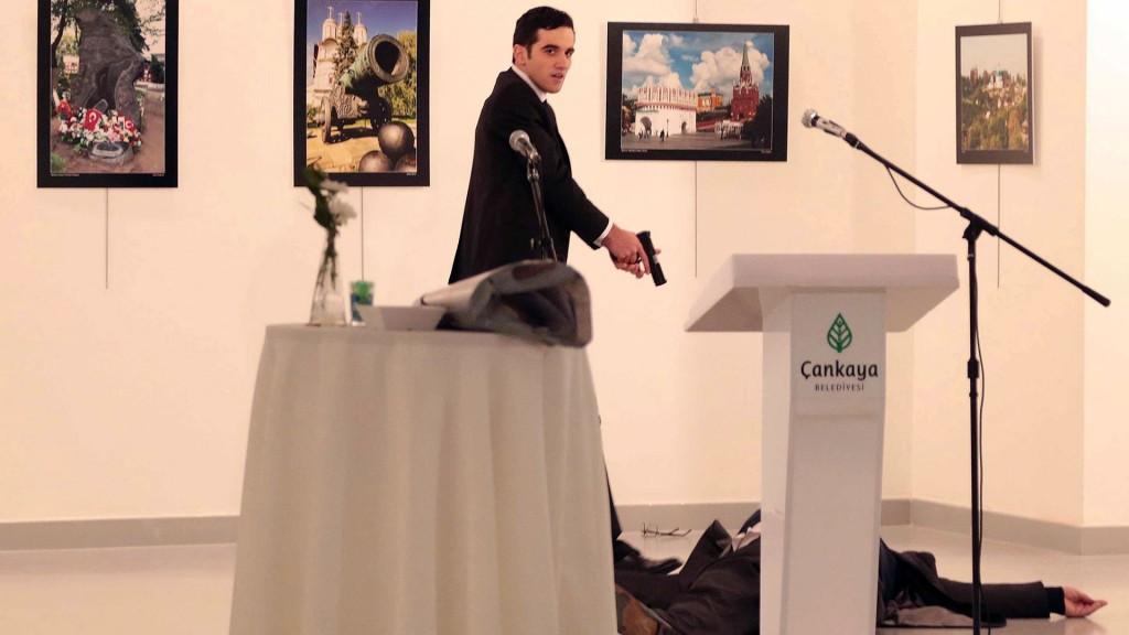 El asesino acaba de ejecutar al embajador y ahora mira hacia el público que asistía al evento (AP)