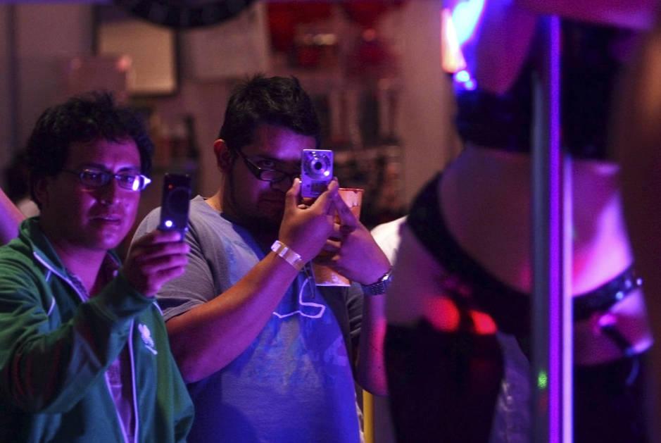 Dos hombres toman fotos de una bailarina durante Expo Erotica 2010. (Reuters/Jorge Duene)