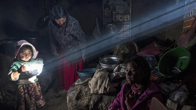 Una niña sostiene un plato de comida caliente mientras la familia Avila almuerza en su casa en Coata, un pequeño pueblo en la orilla del lago Titicaca, en la región de Puno, Perú.