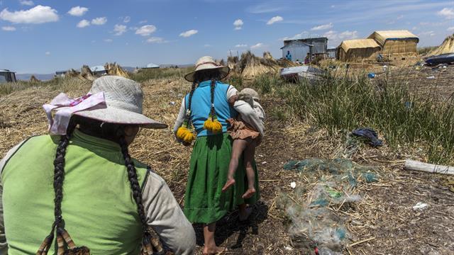 Una mujer lleva a su bebé camino a su casa en Kapi Cruz Grande, una aldea en las orillas llenas de basura del Lago Titicaca en la región de Puno en Perú