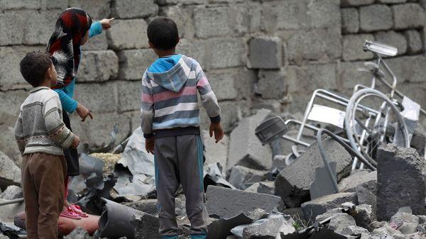 Niños observan los restos de un bombardeo en Saná, capital de Yemen (AFP)
