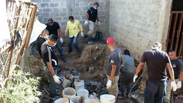 Personal forense trabaja en la remoción de los restos humanos (AFP)