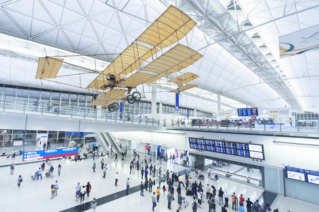 Hong Kong, China – April 15, 2015 : Passengers in the airport main lobby in Hong Kong, China. The Hong Kong airport handles more than 70 million passengers per year.