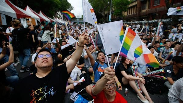 Integrantes de la comunidad LGBT se abrazan mientras celebran la decisión del Tribunal Constitucional sobre el matrimonio entre personas del mismo sexo ante el Parlamento en Taipéi (EFE)